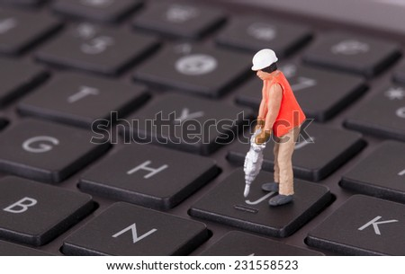 Miniature worker with drill working on a computer keyboard - stock photo