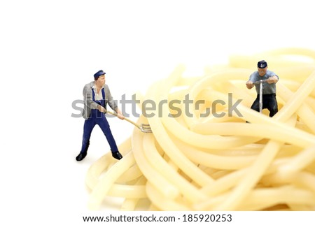 Miniature worker work with spaghetti - stock photo