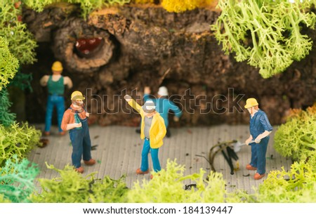 Miniature workers busy clearing a pathway - stock photo