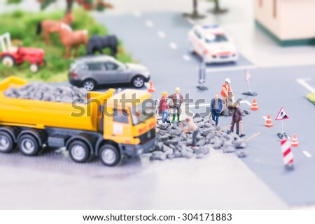 Miniature workers doing road works close up - stock photo