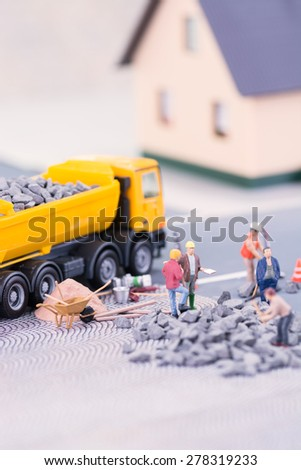 Miniature workers doing road works near a building close up  - stock photo