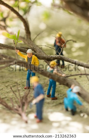 Miniature workmen clearing fallen trees after a storm  - stock photo
