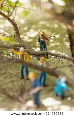 Miniature workmen clearing fallen trees close up  - stock photo
