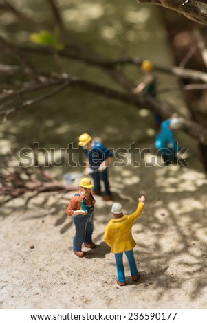 Miniature workmen clearing fallen trees top view  - stock photo