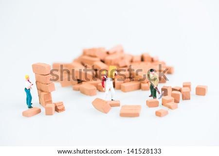 Miniature workmen doing construction brickwork - stock photo