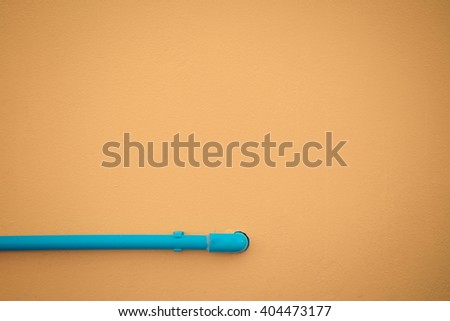 Minimalism style, Blue water pipe on yellow wall texture background. , process in vintage style - stock photo