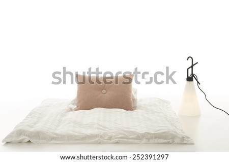Minimalist modern living area with a comfortable soft plain white comforter with beige cushion on the floor alongside a contemporary design conical lamp over a white background with copyspace - stock photo