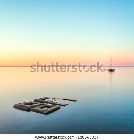 minimalist seascape with rocks & ship - stock photo