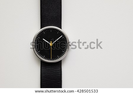 Minimalist wristwatch black dial on white background - stock photo