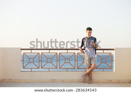Minimalistic portrait of young happy smiling man holding cellphone, using app, making call, messaging text or dialing number, standing barefoot on summer street with sea scenery, copy space - stock photo