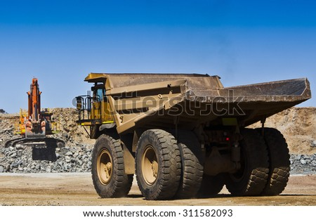Mining scene. Large truck drives towards digger to fill with ore from open cast mine. All logos removed. - stock photo