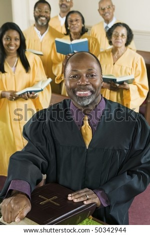 Minister at altar with Bible, gospel choir in background, portrait - stock photo