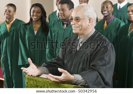 Minister Preaching in Front of Gospel Choir - stock photo