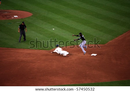 MINNEAPOLIS - JULY 17:  Alexi Ramirez of the White Sox jumps over Joe Mauer of the Twins to complete at double play in a game at Target Field July 17, 2010 in Minneapolis, MN. - stock photo