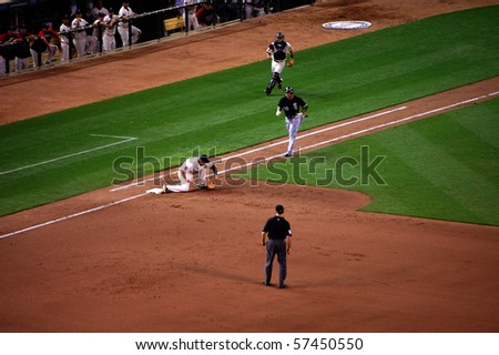 MINNEAPOLIS - JULY 17:  Carlos Quentin of the White Sox runs down the line as Michael Cuddyer of the Twins catches the ball for the final out at Target Field July 17, 2010 in Minneapolis, MN. - stock photo