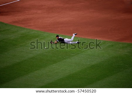 MINNEAPOLIS - JULY 17:  White Sox second baseman Gordon Beckham dives while attempting to make a play but misses in a game against the Twins at Target Field July 17, 2010 in Minneapolis, MN. - stock photo