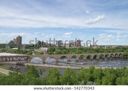 MINNEAPOLIS - JUN 16: Downtown Minneapolis, MN at noon time on Jun 16, 2013 as seen the Stone Arch bridge. It's a former railroad bridge crossing the Mississippi River at Saint Anthony Falls. - stock photo