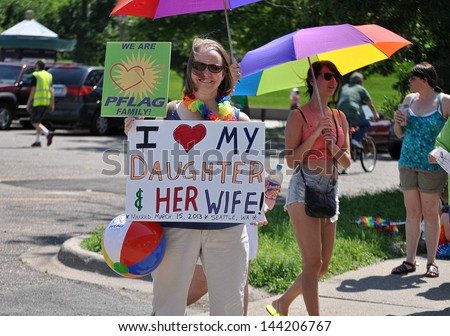 MINNEAPOLIS - JUNE 30:  An unidentified PFLAG Mother shows support for her Daughter at the Twin Cities Gay Pride Parade on June 30, 2013, in Minneapolis. - stock photo