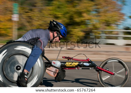 MINNEAPOLIS, MN - OCTOBER 3: Sam Tebaka speeds past at Mile 19 and goes on to finish 9th in the Men's Wheelchair Division of the 2010 Medtronic Twin Cities Marathon, October 3, 2010 in Minneapolis, MN - stock photo