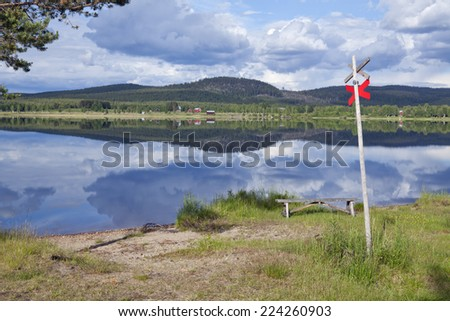 Minor buildings, farm along the river. Meadows, hills, rock and a gently river this side. Reflections in the water. Snowmobile sign, track this side the river. - stock photo