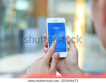 MINSK, BELARUS - JULY 05, 2014: Woman holding brand new black Apple iPhone 5S. Skype is a voice-over-IP service and instant messaging client. - stock photo