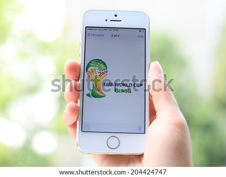 MINSK, BELARUS - JULY 12, 2014: Woman holding brand new white Apple iPhone 5S. The official logo of the football World Cup in Brazil. - stock photo