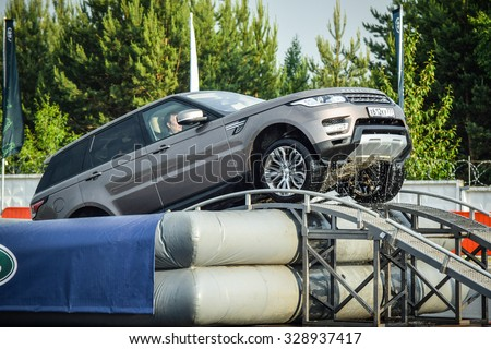MINSK, BELARUS - JUNE 20, 2015: Test-drive event for 2015 model year Land Rover and Range Rover is held in Minsk, Belarus on June 20, 2015. British SUV Range Rover Sport leaves an artificial pond. - stock photo