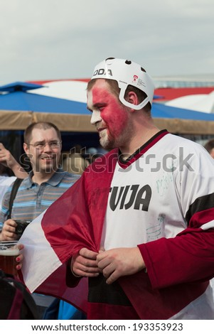 MINSK, BELARUS - May 17, 2014: ICE HOCKEY WORLD CHAMPIONSHIP, MINSK-ARENA, The hockey fan from Latvia with national flag in the uniform of a national team of Latvia - stock photo