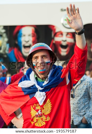 MINSK, BELARUS - May 18, 2014: ICE HOCKEY WORLD CHAMPIONSHIP, MINSK-ARENA, The hockey fan from Russia with national flag in the uniform of a national team of Russian Federation - stock photo