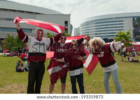 MINSK, BELARUS - May 17, 2014: ICE HOCKEY WORLD CHAMPIONSHIP, MINSK-ARENA, The hockey fans from Latvia with national flags in the uniform of a national team of Latvia - stock photo