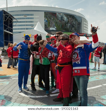MINSK, BELARUS - May 17, 2014: ICE HOCKEY WORLD CHAMPIONSHIP, MINSK-ARENA, The hockey fans from Latvia with national flags in the superheroes costumes - stock photo