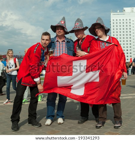 MINSK, BELARUS - May 17, 2014: ICE HOCKEY WORLD CHAMPIONSHIP, MINSK-ARENA, The hockey fans from Switzerland with national flag and accessories, in national costumes - stock photo