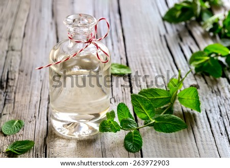 Mint essential oil in a glass bottle - stock photo