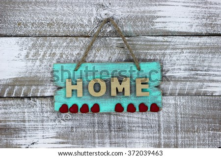 Mint green HOME sign with red hearts hanging on antique rustic white wood background; Valentine's Day, family and love concept - stock photo