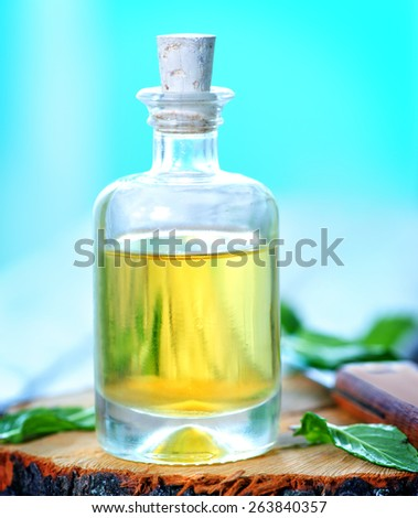 mint oil in glass bottle and on a table - stock photo