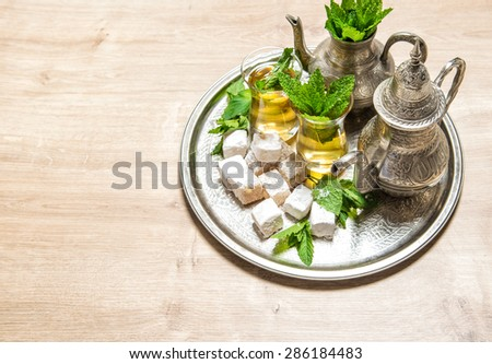 Mint tea with traditional arabic delight. Oriental hospitality concept. Holidays table setting. - stock photo