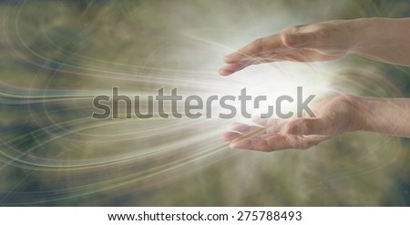 Miracles Happen - pair of parallel female healer's hands with an intricate white light energy formation between on a wide muted gold background with plenty of copy space - stock photo