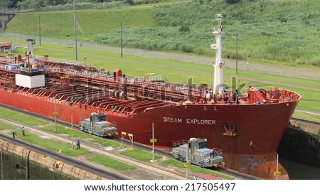 Miraflores locks, Panama - August 5th of 2014: Red large cargo ship entering Miraflores Locks, where vessels are lifted (or lowered) 54 feet (16.5 m) allowing them to go from Pacific to Caribbean Sea. - stock photo