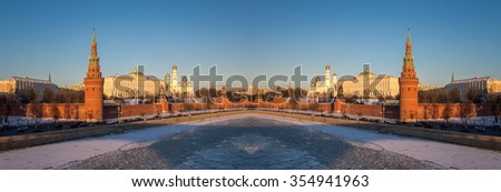 Mirror image of red walls of sunset Kremlin in Moscow near iced river in winter - stock photo