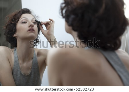 Mirror image of woman applying mascara - stock photo