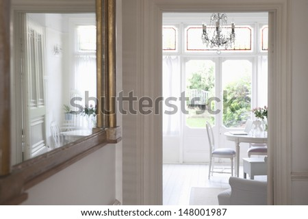 Mirror in hallway with view of living room - stock photo
