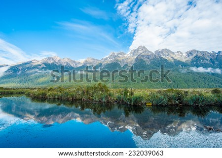 Mirror Lakes are a famous natural landmark omn the Milford Road in the Fiordland National Park. Snowy mountains are reflecting in a calm water. New Zealand - stock photo