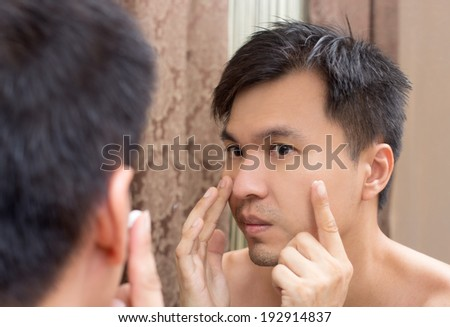 Mirror reflection of a young asian handsome man applying facial cream on face - stock photo