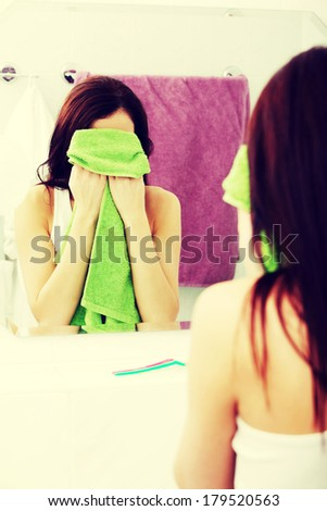 Mirror reflection of a young woman wiping her face with a green towel in the bathroom. - stock photo