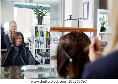 Mirror reflection of young woman getting a hairdo by beautician at parlor - stock photo