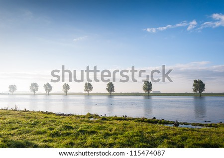 Mirror smooth water surface of a Dutch river at dawn. - stock photo