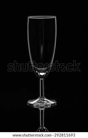 Mirrored transparent wine glass on isolated black background - stock photo