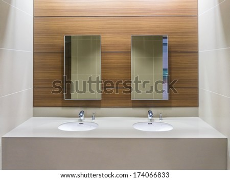 Mirrors and washbasins in restroom - stock photo