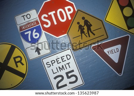 Miscellaneous road signs on a gray wall - stock photo