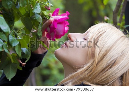 Miss  smelling a rose in a baroque garden - stock photo